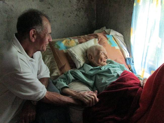 viejito enfermo acostado en su cama
