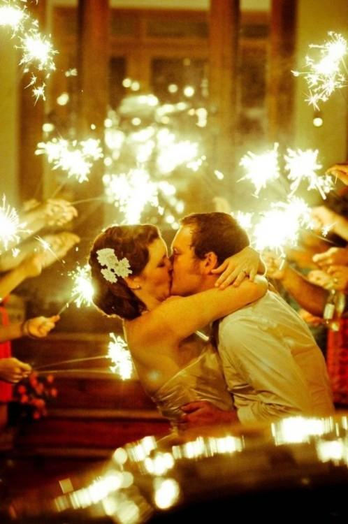novios besandose entre bengalas