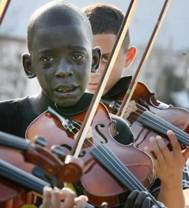 niño llorando mientras toca el violin