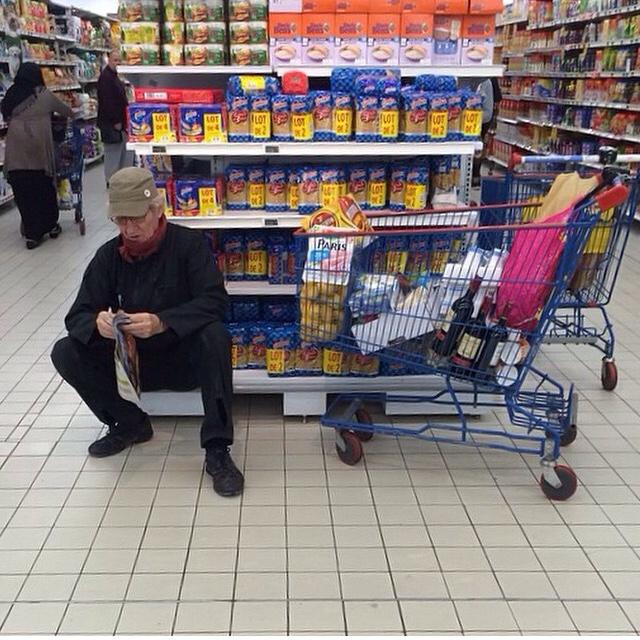 señor sentado mientras hace compras en el supermercado
