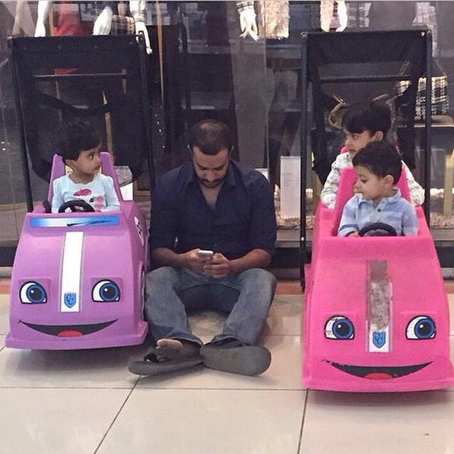 señor jugando con el celular mientras cuida a sus hijos