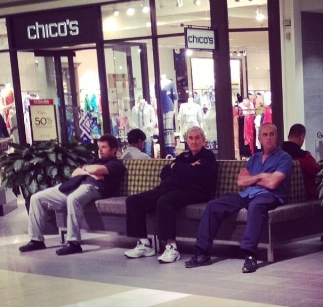 señores sentados en una banca fuera de una tienda de nombre chicos