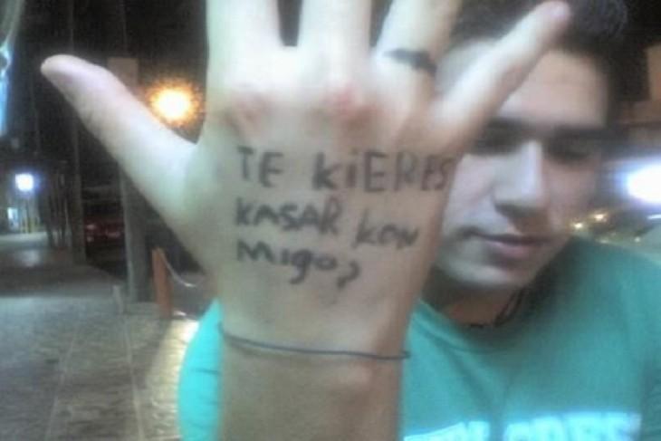 """fotografía de un chico con la frase """"te quieres casar conmigo"""" en una mano"""