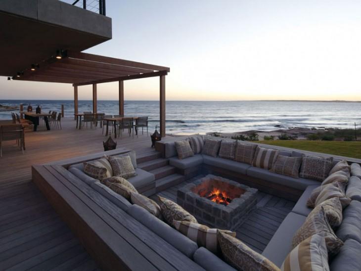 pequeña sala a la orilla de una playa con una chimenea en el centro