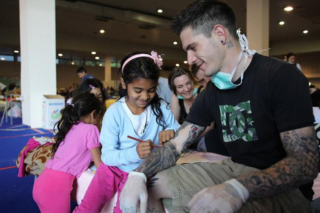 niña haciendole un tatuaje a un soldado