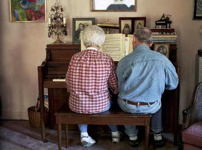 señor enseñando a su esposa a tocar el piano