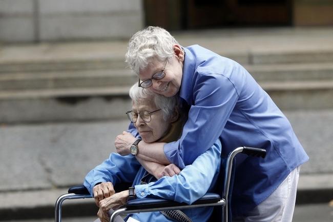 señor abrazando a señora en silla de ruedas