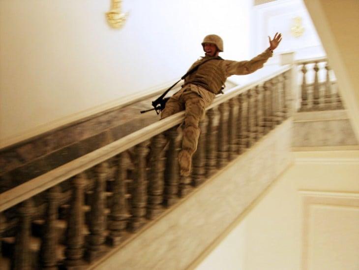 soldado resbalandose por el pasamanos de una escalera