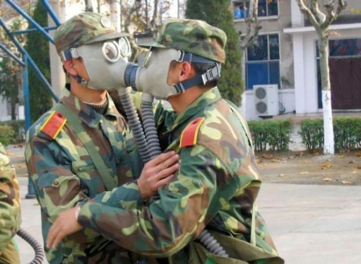 soldados dandose un beso con mascarillas puestas