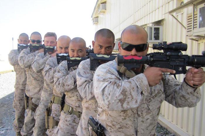 soldados con un arma que tiene pintado unos bigotes de colores