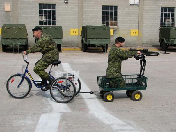 soldado en una bicicleta estirando un carrito