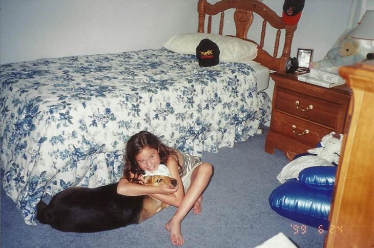 niña sentada en el suelo abrazando a su perrita