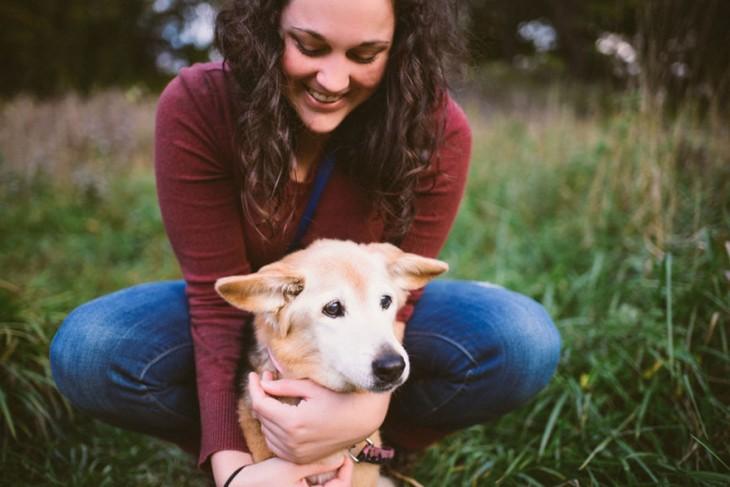 muchacha sentada en el pasto abrazando a su perro