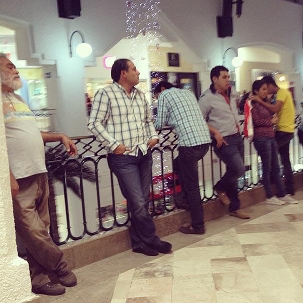 fila de hombres de pie esperando fuera de una tienda