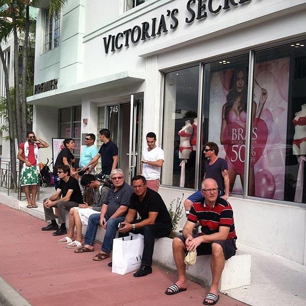 hombres sentados afuera de tienda de victoria secret