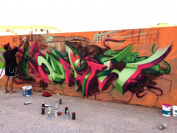 Un hombre pintando un grafiti sobre una pared
