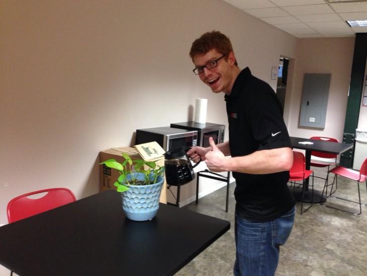 empleado dandole cafe a una planta