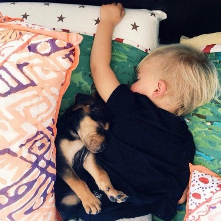 bebe dormido boca abajo y el perro en su axila