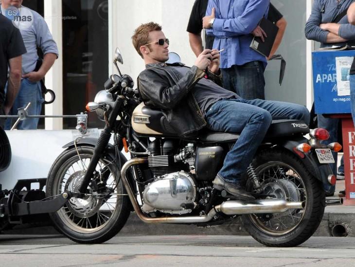 chico recostado sobre una moto mira el telefono