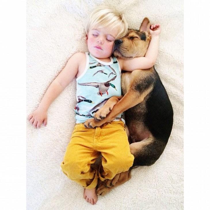 niño con pantalon amarillo dormido con el perro