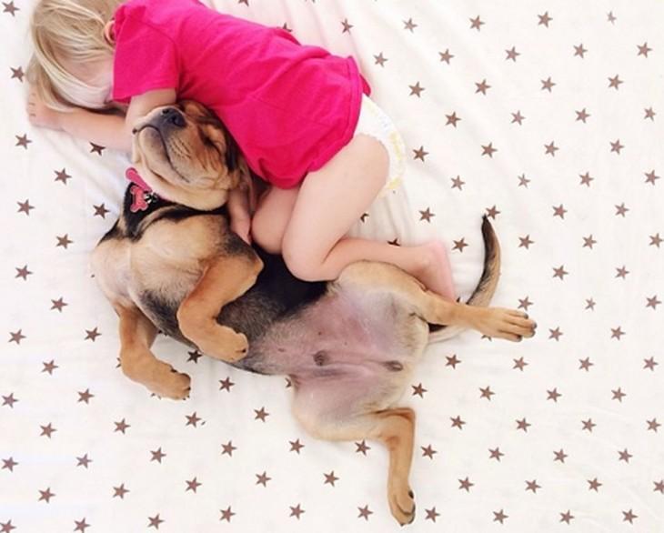sabana con puntos rojos y niño dormido con perro pastor aleman