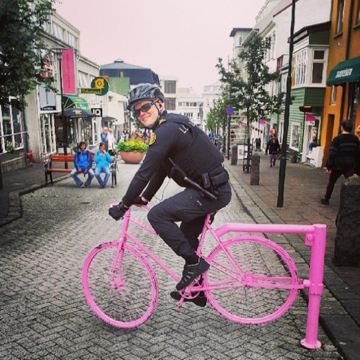 policía en bicicleta rosada