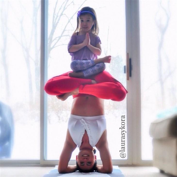 posicion de yoga con la cabeza y la niña arriba de ella