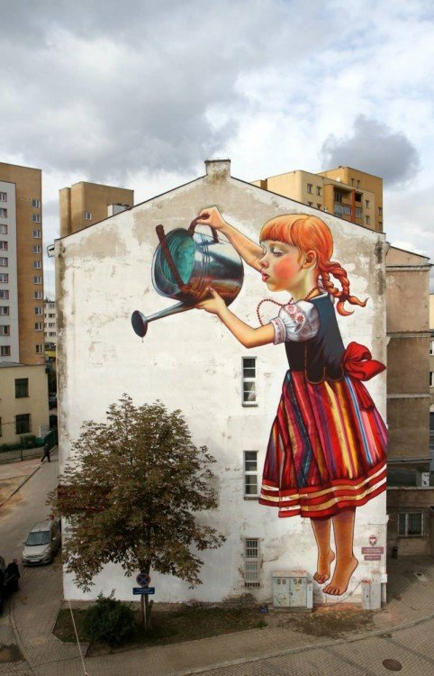 niña con unv estido de colores y trenzas regando un arbol