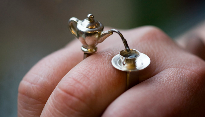 anillo con una tetera de plata sirviendo cafe