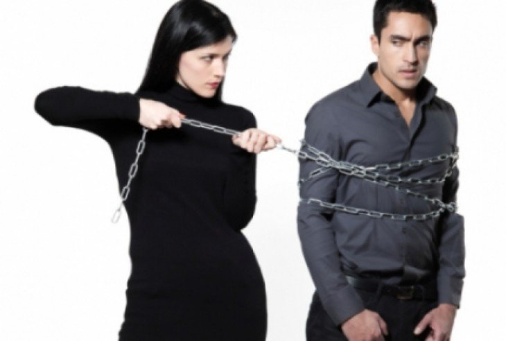 mujer que tiene amarrado con una cadena a un hombre