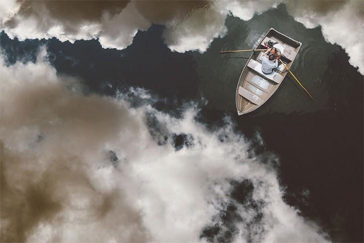 novios en una lanccha con el reflejo del cielo