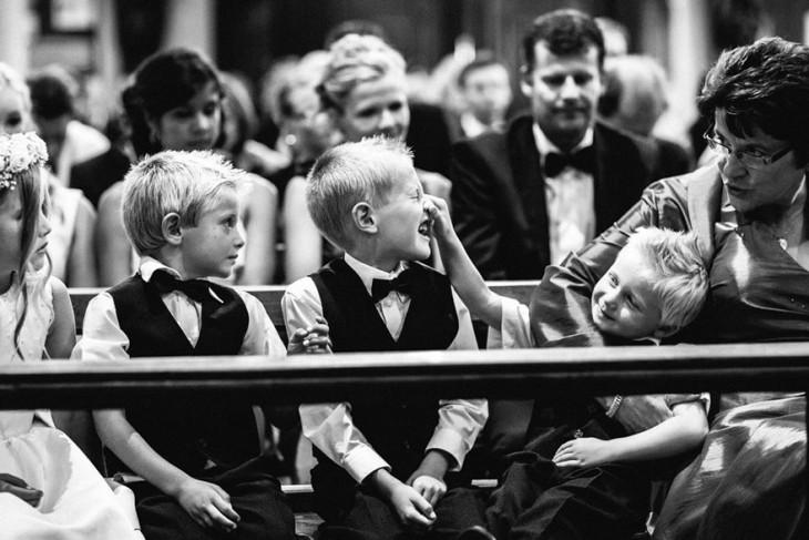 niños jugando en misa mientras que la abuela los regaña