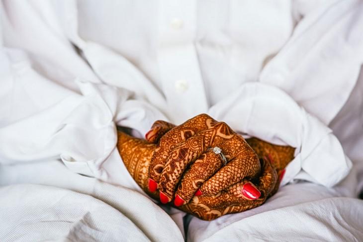 anillo de compromiso en la mano de una mujer que las tiene tatuadas