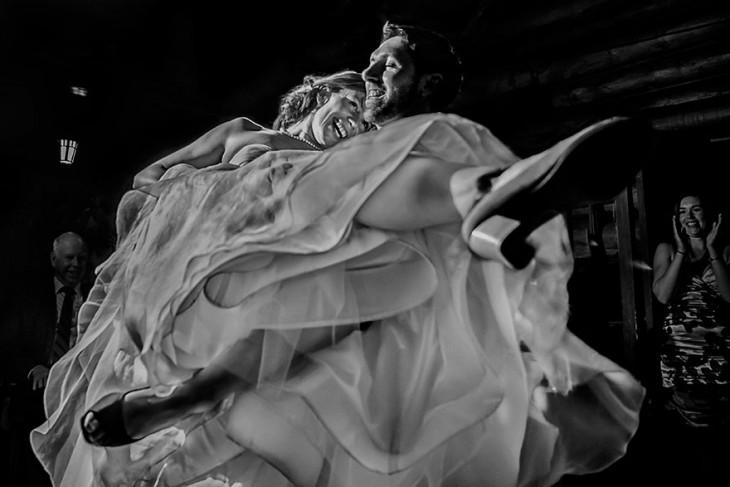 hombre cargando mujer en brazos depues de la boda