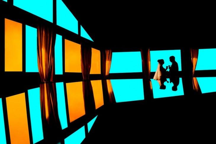 un brindis de los novios en un salon con vidrios de colores