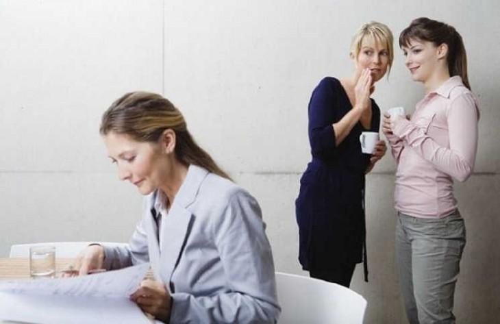 dos mujerse criticando a su compañera de trabajo