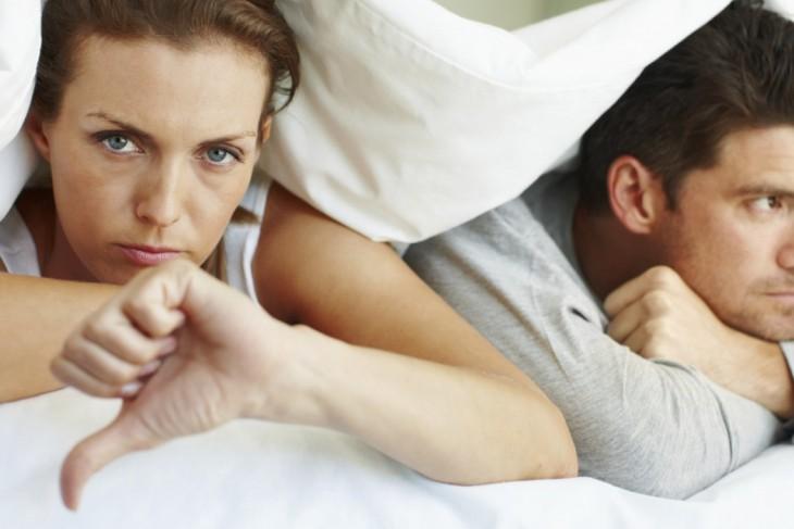pareja que se encuentran acostados y la mujer haciendo señal de desaprobacion