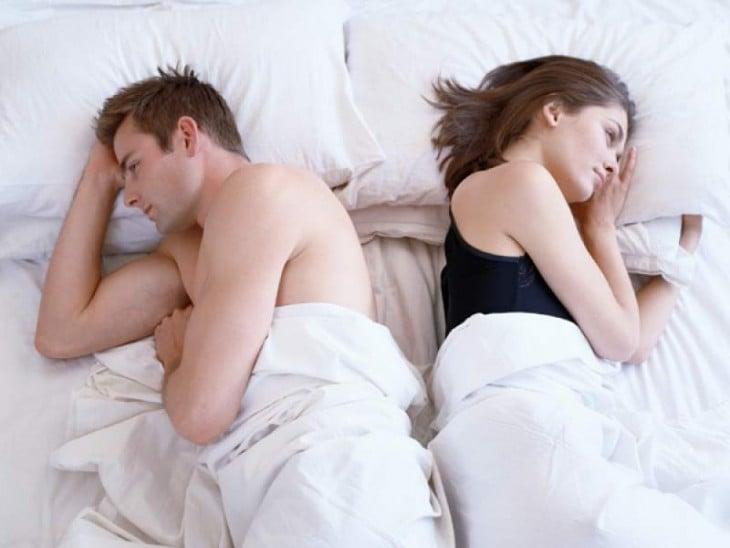 pareja acostados estan disustados cada uno volteado de lado contrario