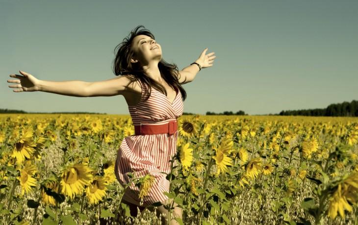 mujer feliz corriendo en un jardin lleno de girasoles