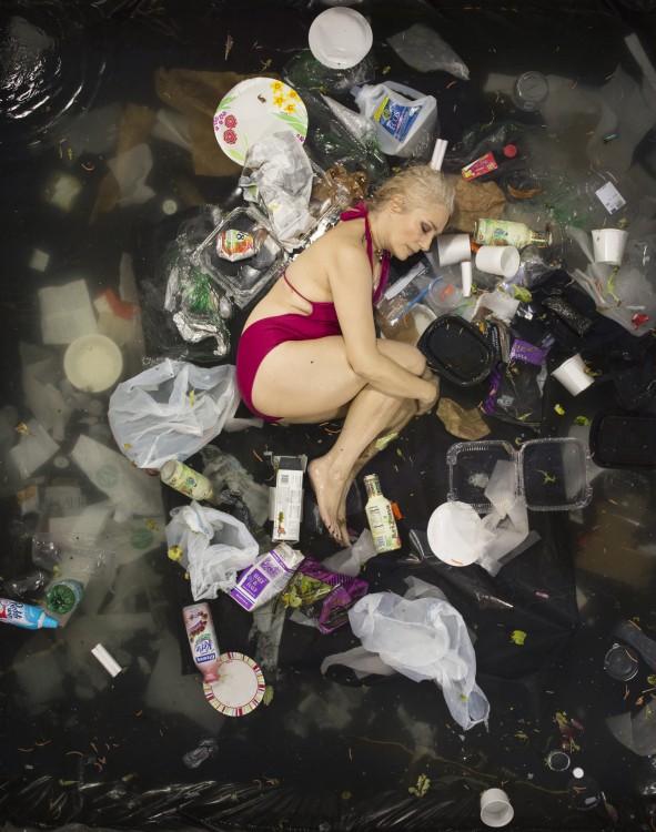 Gregg Sega fotografía chica en posicion fetal en medio de la basura acumulada durante 7 dias