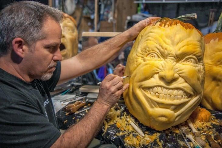 hombre que esta esculpiendo una calabaza de halloween
