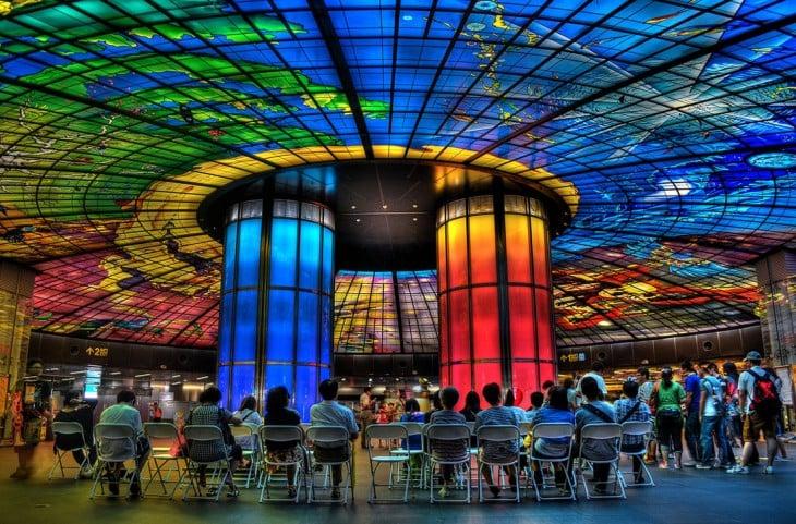 colorida estacion del metro que presenta luces en el techo y en dos pilares