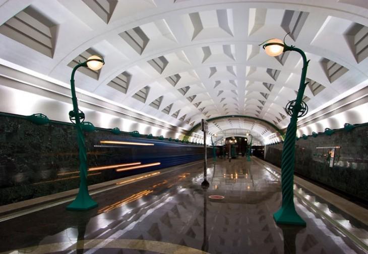pasillo de una estacion de metro con largos faroles de color verde