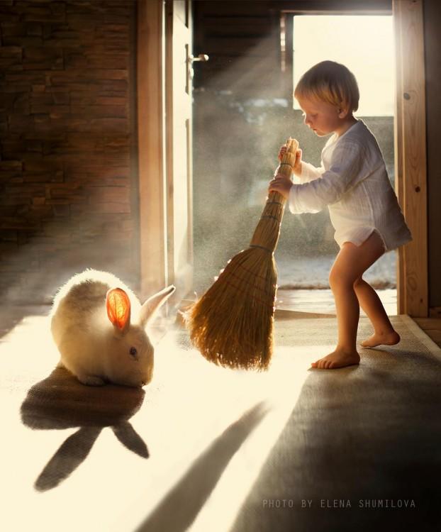niño barriendo y conejo