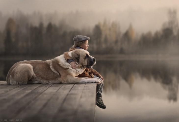 niño y perro en muelle del lago
