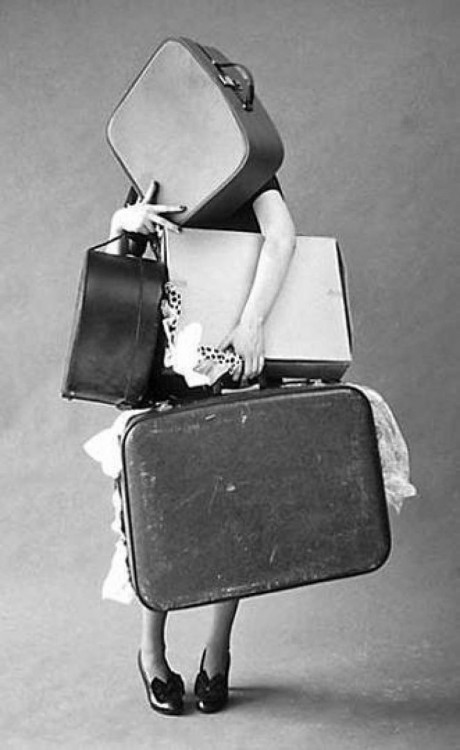 mujer cargando cuatro maletas pesadas