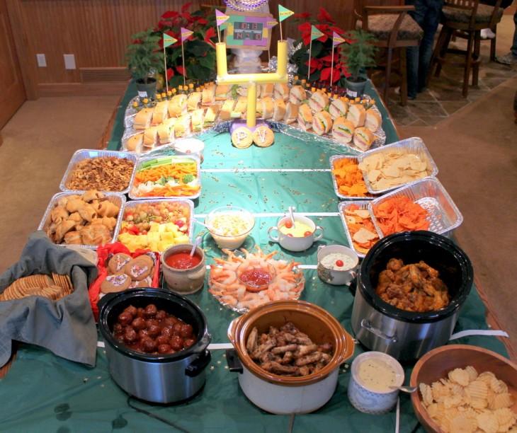 mesa adornada con diferentes tipos de botanas y forma un estadio de ftubol