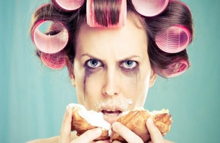 mujer con tubos y despintada de los ojos comiendo un pan