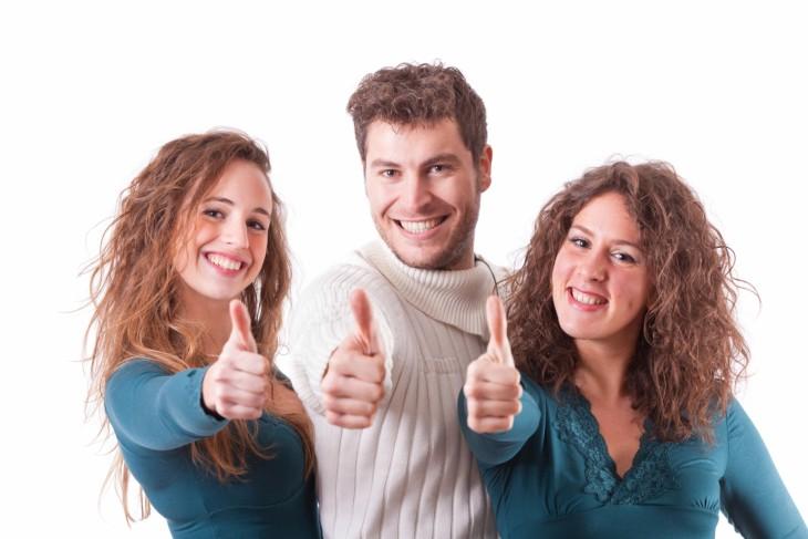 dos mujeres y un hombre positivos con el dedo para arriba