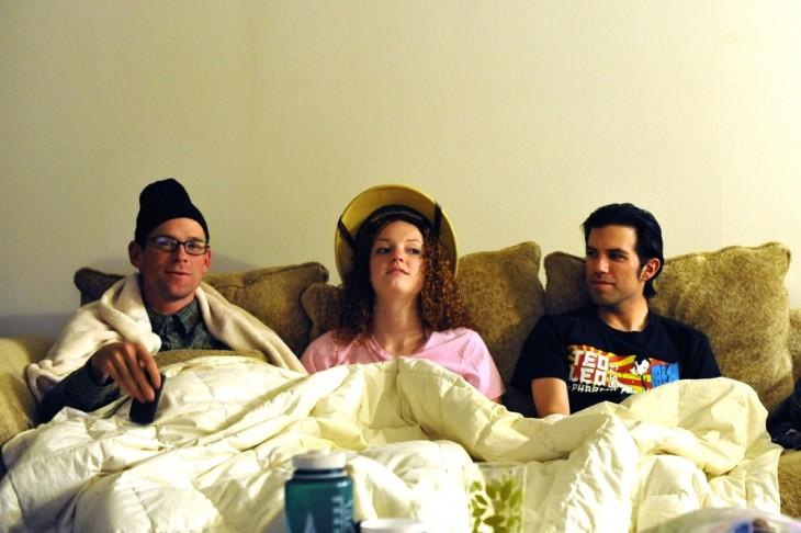 tres personas costadas en una cama